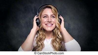 Beautiful blonde listens to music on headphones on a dark...