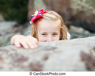 beautiful blonde little girl girl hides behind a stone