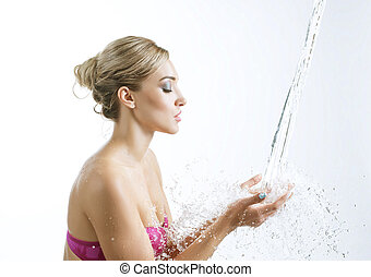 Beautiful blonde looking at water stream in hands