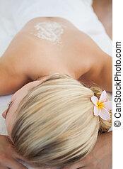 Beautiful blonde lying on massage table with salt scrub treatmen