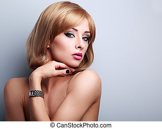 Beautiful blonde makeup female model posing in fashion watches on the hand