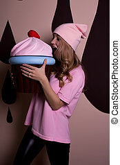 Beautiful blonde model with wavy hair in pink cap biting a big cupcake on a pink background. Holiday concept