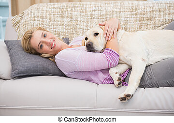 Beautiful blonde on couch with pet dog at home in the living...
