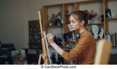 Beautiful blonde painter is painting picture in art studio...