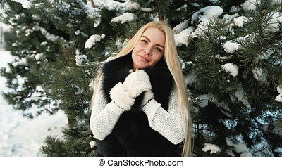 Beautiful blonde poses for photographer, winter landscape