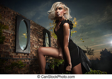 Beautiful blonde posing over evening sky