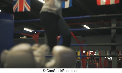 Beautiful blonde practicing blows. Moving video to boxing gloves in the ring
