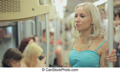 Beautiful blonde reading in a crowded metro car