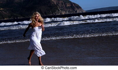 Beautiful blonde running in white dress on sunny day at the...