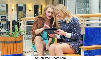 Beautiful blonde sitting bench with store and watching something on a tablet