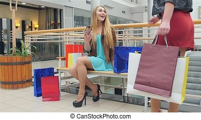 Beautiful blonde sitting on a bench Mall. Slow motion