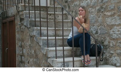 Beautiful blonde sitting on the stone steps and eat a meal.