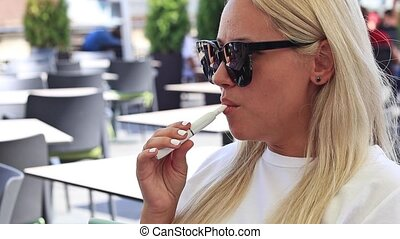beautiful blonde smoke electronic cigarette in public...