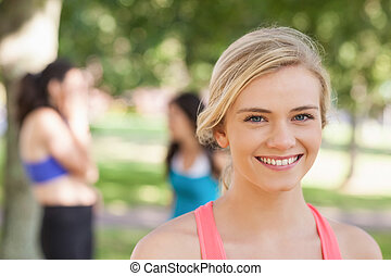 Beautiful blonde sporty woman posing in a park