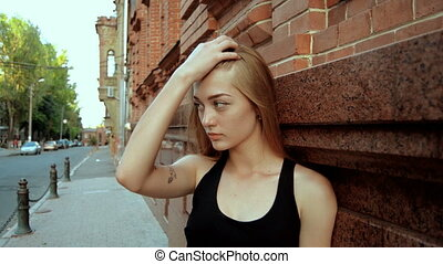beautiful blonde stands on the street and straightens your hair