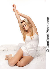 Beautiful blonde stretching in bed