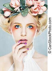 Beautiful blonde supermodel in wreath of flowers studio shot...