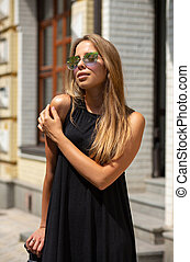 Beautiful blonde tanned woman in glasses, posing at the avenue in a sunny day