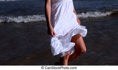 Beautiful blonde walking in white dress on sunny day at the...
