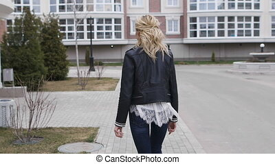 beautiful blonde walking on the sidewalk around the stylish home. She is a young