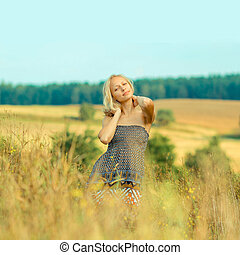 beautiful blonde walks into the field. portrait of a beautiful blonde in a field in spring