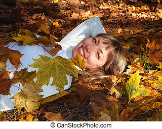 Beautiful blonde with leaves in the autumn forest