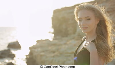 Beautiful blonde with long hair wearing a black dress laughing near the sea at sunset in the mountains