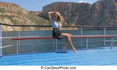 Beautiful blonde with long hair which fluttering in the wind sits on the pleasure boat that is in the sea