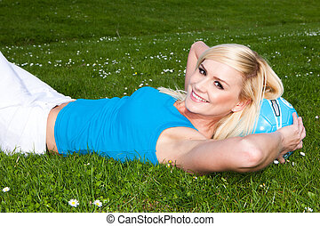 Beautiful blonde with lovely smile on grass