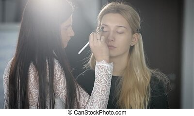 Beautiful blonde with thin eyebrows, long hair waits for the makeup. Makeup artist does a professional makeup, it is now at the stage of applying eye shadow on the closed eyelids to the young girl