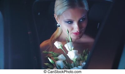 Beautiful blonde with white roses posing in the car