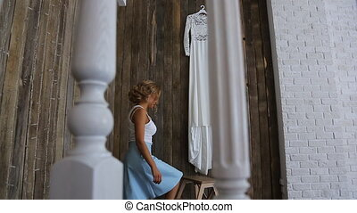 Beautiful blonde woman climbs on small stepladder to take her wedding dress.