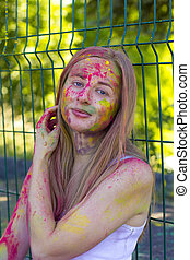 Beautiful blonde woman covered color powder Holi