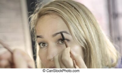 Beautiful blonde woman doing everyday makeup in front of mirror, draws eyebrows with a small brush