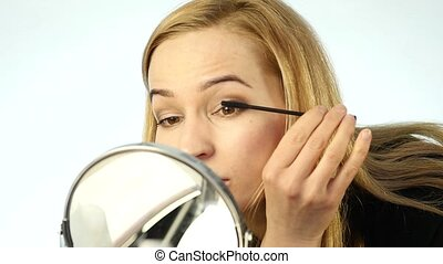 Beautiful blonde woman doing everyday makeup in front of...