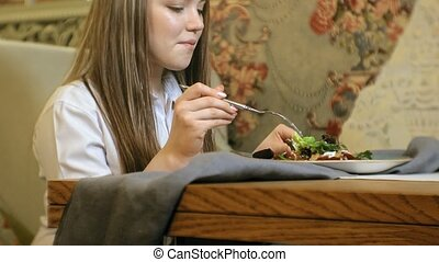 Beautiful blonde woman eating and drinking in restaurant, lunch break