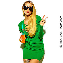 beautiful blonde woman girl in casual hipster summer clothes with no makeup isolated on white drinking cola from bottle with straw giving a kiss and showing peace sign