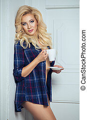 Beautiful blonde woman holding cup on white wall