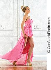 Beautiful blonde woman in a pink evening long dress.