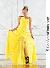 Beautiful blonde woman in a yellow evening dress.