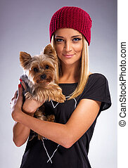 Beautiful blonde woman in autumn dress, holding a yorkshire terrier dog
