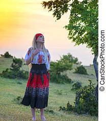Beautiful blonde woman in old-fashioned dress at sunset