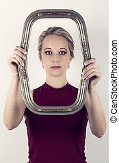 Beautiful blonde woman in red top holding a portrait frame in front of face
