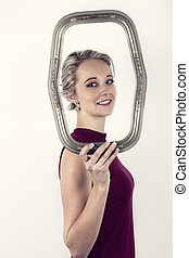 Beautiful blonde woman in red top side on holding a portrait frame in front of her face