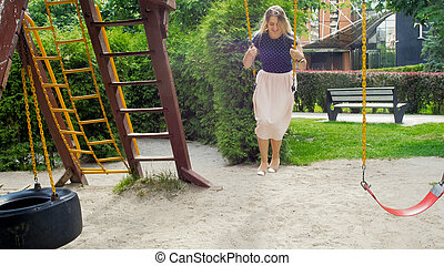 Beautiful blonde woman in skirt riding on swing at park