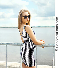 Beautiful blonde woman in sunglasses and striped dress over sea