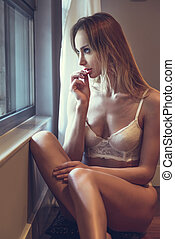 Beautiful blonde woman in white lingerie posing near a window.