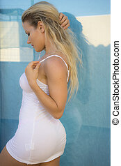 beautiful blonde woman in white shirt posing on a terrace set beside the sea in summer, Spain