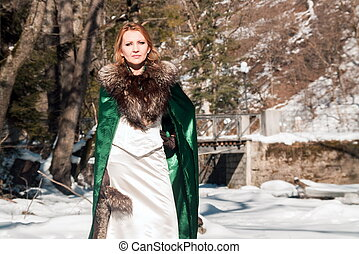 Beautiful blonde woman in winter clothes in the park
