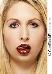 beautiful blonde woman licking chocolate from her chocolate covered lips on white background